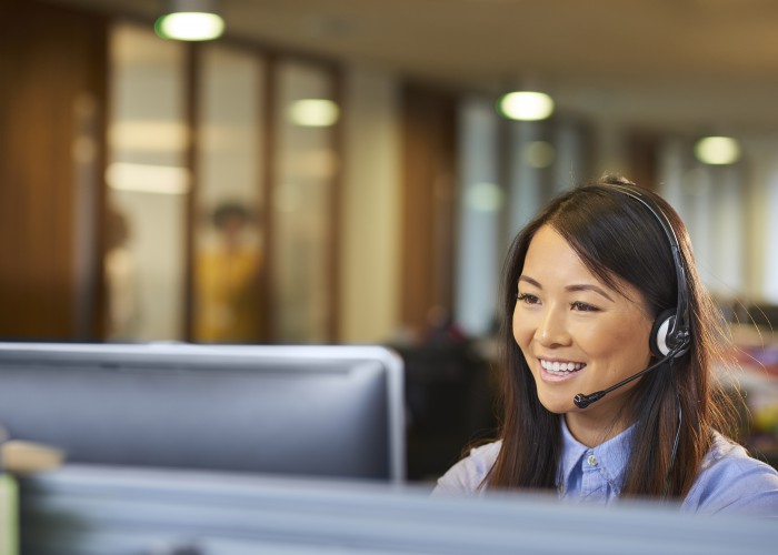a young call centre representative greets a caller in a large open plan office . Co-workers can be seen defocussed in the background .